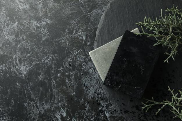 Taca z naturalnym mydłem ręcznie robionym na czarnym tle smokey