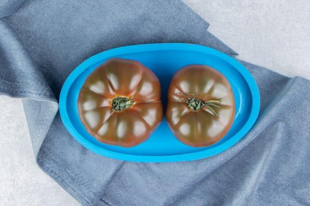 Taca z pomidorami na ręczniku, na marmurowej powierzchni