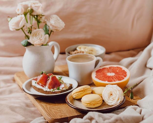 Taca z poranną kawą i kanapką w łóżku