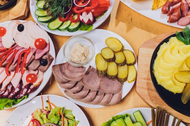 Taca z pysznym salami, kawałkami szynki, kiełbasą i sałatką. talerz z mięsem z wyborem na stole.