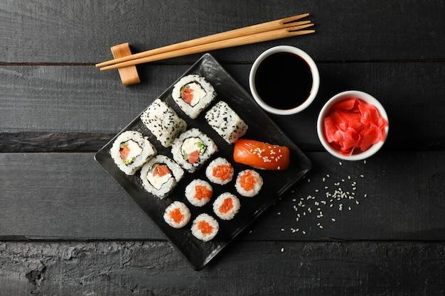 Taca z pysznymi rolkami sushi na drewnianej powierzchni. japońskie jedzenie