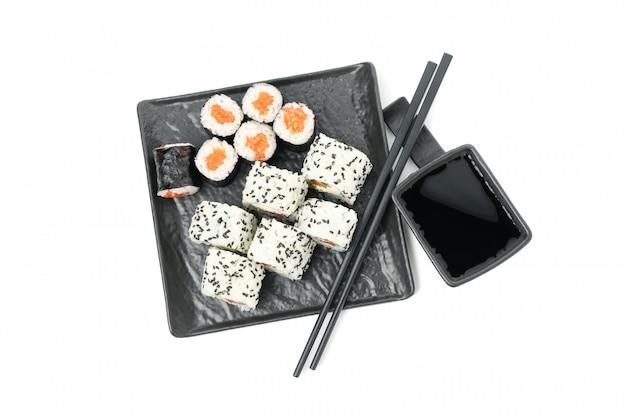 Taca z rolkami sushi, pałeczkami i sosem sojowym na białym tle