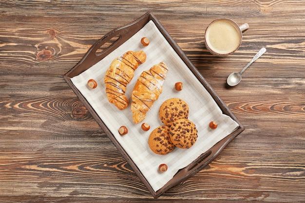 Taca ze smaczną piekarnią i filiżanką kawy na drewnianym stole