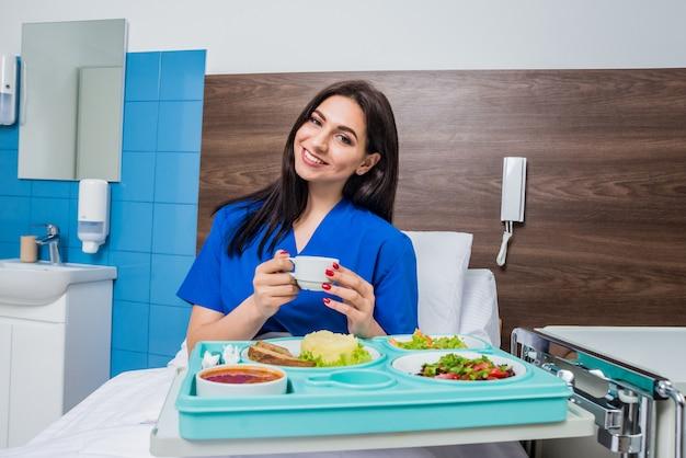 Taca ze śniadaniem dla młodej pacjentki. młoda kobieta je w szpitalu.