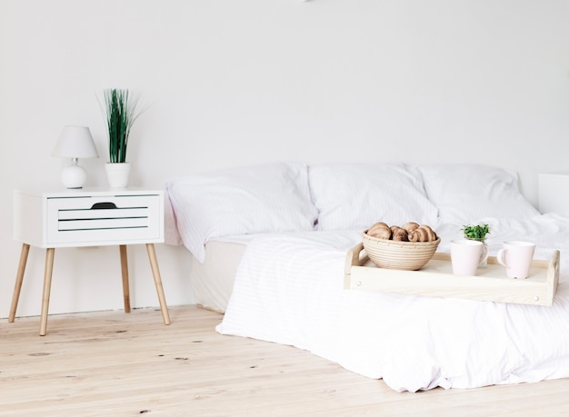 Taca ze śniadaniem na łóżku w jasnej sypialni
