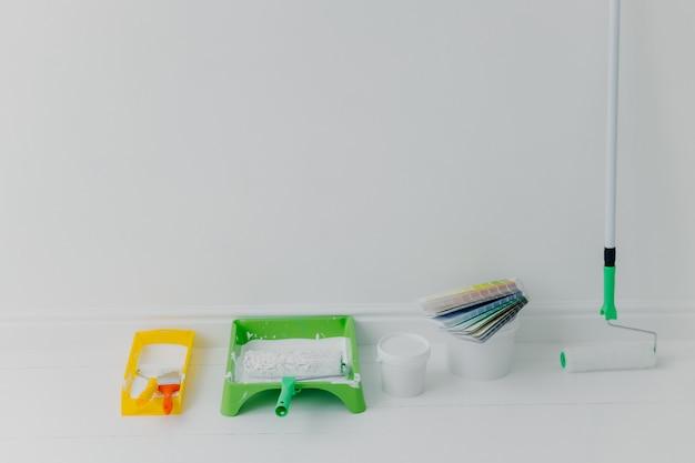 Tace z wałkami do malowania, wiadro z kolorami i próbkami kolorów. koncepcja remontu domu.
