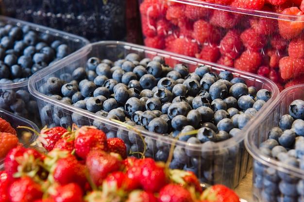 Tace ze świeżymi jagodami na wystawie na lokalnym rynku.