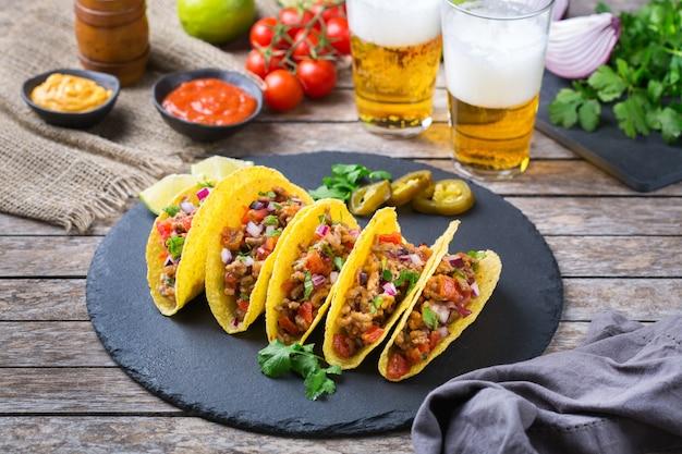 Taco shell ellow corn tortilla chips nachos z mieloną wołowiną, mielonym mięsem, guacamole, czerwoną gorącą salsą jalapeno chili i sosem serowym z tequilą lub piwem na stole.