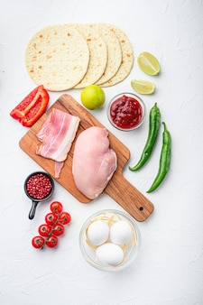 Taco składniki domowej roboty autentyczny meksykański posiłek z kurczaka, na białym betonowym tle widok z góry.