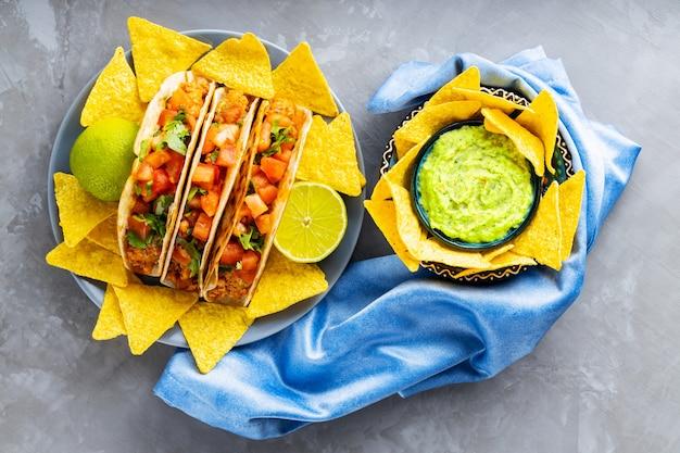 Tacos i chipsy tortilla na szarym tle. meksykańskie taco, chipsy nacho i sos guacamole na niebieskiej serwetce. hiszpanie meksykańskie jedzenie. skopiuj miejsce. widok z góry