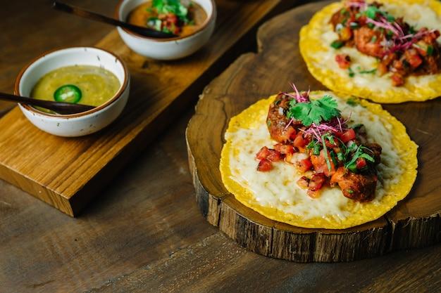 Tacos z kurczaka z grilla z sałatką z pomidorów podawane na drewnianej desce do krojenia.