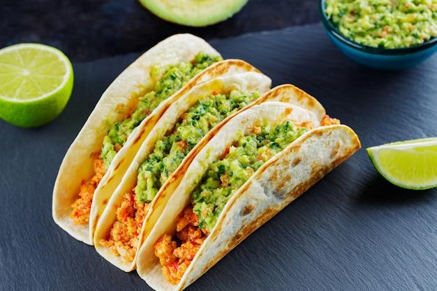 Tacos z kurczakiem i guacamole na ciemnym tle. meksykańskie tacos ze smażonym mięsem mielonym na łupkowej desce. tradycyjne danie kuchni meksykańskiej