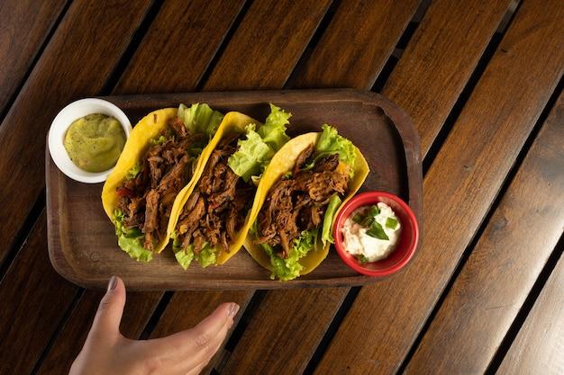 Tacos z mięsa. tradycyjne meksykańskie jedzenie. ręczne łapanie taco.