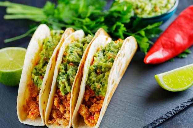 Tacos ze smażonym mięsem mielonym i sosem guacamole na ciemnym tle. meksykańskie tacos i składniki na tablicy łupkowej. hiszpańskie jedzenie?