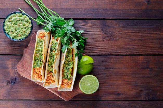 Tacos ze smażonym mięsem mielonym i sosem guacamole na drewnianych deskach. meksykańskie tacos, kolendra i limonka na drewnianym tle. kuchnia meksykańska. styl rustykalny