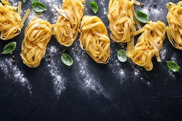 Tagliatelle. domowy makaron, liście bazylii, mąka, papryka, oliwa z oliwek i pomidorek koktajlowy na ciemnym czarnym tle. koncepcja żywności. makieta. poziomo z miejsca na kopię.