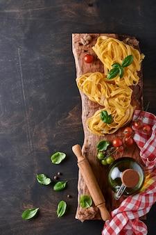 Tagliatelle. domowy makaron, liście bazylii, mąka, pieprz, oliwa z oliwek, pomidor koktajlowy i wałkiem i nóż do makaronu na ciemnym starym drewnianym tle. koncepcja żywności. makieta. poziomo z miejsca na kopię.