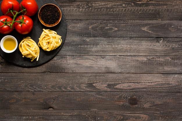 Tagliatelle z pomidorem i bazylią, wykonane w domu, na drewnianej powierzchni.