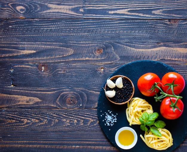 Tagliatelle z pomidorem i bazylią, wykonane w domu na drewnianym stole