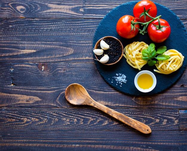 Tagliatelle z pomidorem i bazylią, wykonane w domu, na drewnianym tle.
