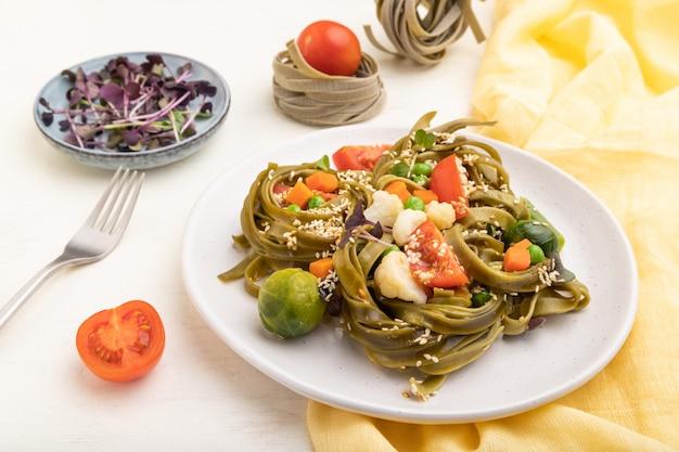 Tagliatelle zielony szpinak makaron z pomidorów, grochu i mikrogreen kapusty na białym tle drewnianych.