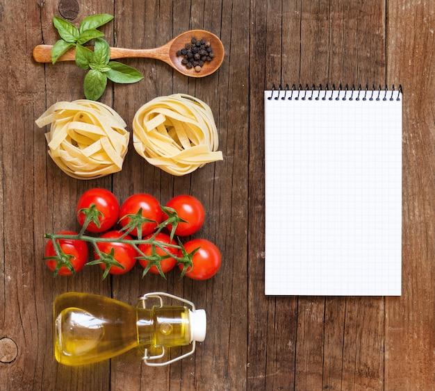 Tagliolini makaron, surowe warzywa, olej oliwkowy i notatnik kopia przestrzeń na starym drewnianym blatem