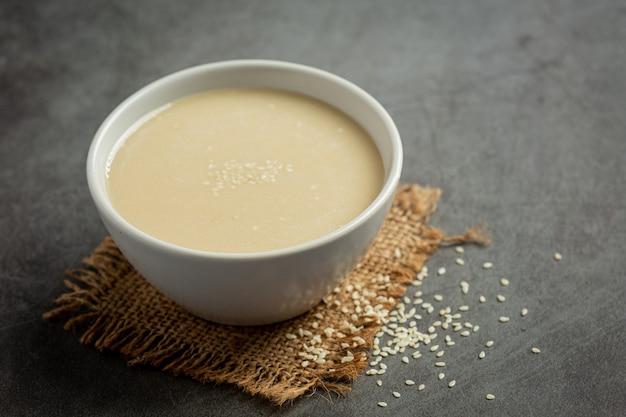 Tahini i nasiona sezamu na ciemnym tle