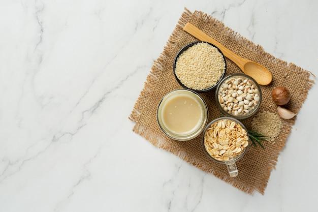 Tahini i nasiona sezamu na marmurowym tle