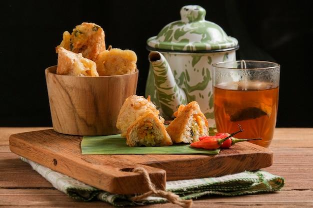 Tahu susur podaje się na desce do krojenia z kawałkami, które pokazują zawartość. to tradycyjna potrawa z indonezji, zrobiona ze smażonego tofu wypełnionego smażonymi warzywami zawiniętymi w ciasto mączne