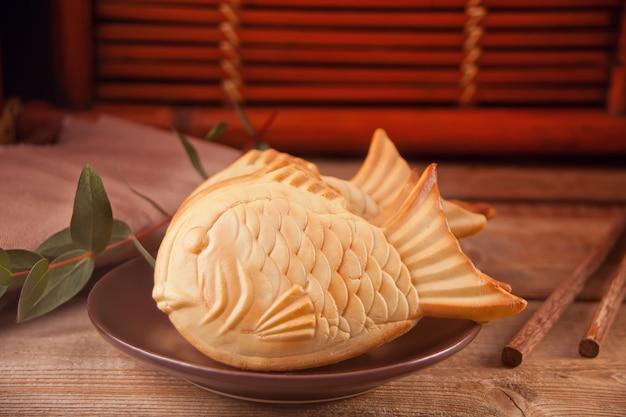 Taiyaki japoński ulicy żywności w kształcie ryby słodki nadzienie waflowe na drewnianym stole.