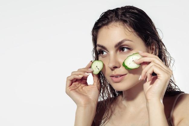 Tajemnice młodości. piękna młoda kobieta nad biel ścianą. kosmetyki i makijaż, leczenie naturalne i ekologiczne, pielęgnacja skóry.