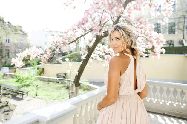 Tajemnicza blond dziewczyna w białej sukni wygląda przez ramię