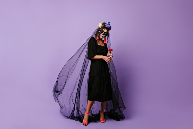 Tajemnicza kobieta delikatnie trzyma czerwoną różę. dziewczyna z makijażem na halloween w czarnej sukience i welonie.