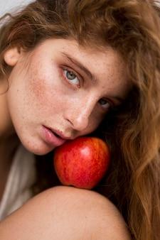 Tajemnicza kobieta pozuje z bliska czerwone jabłko