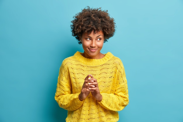 Tajemnicza kobieta zaciera dłonie i knuje coś z kolcami w palcach ma w głowie wspaniały plan ubrana w dzianinowy żółty sweter odizolowany na niebieskiej ścianie podpowiada z uśmiechem
