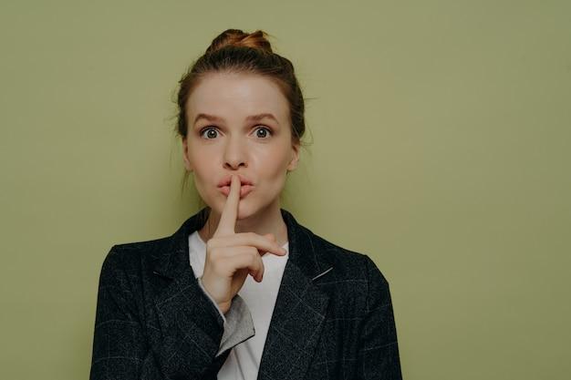 Tajemnicza młoda kobieta w stroju casual, prosząca o milczenie lub zachowanie czegoś w tajemnicy, młoda kobieta robiąca gest wyciszenia lub ciszy palcem na ustach, stojąc w studio. koncepcja tajności