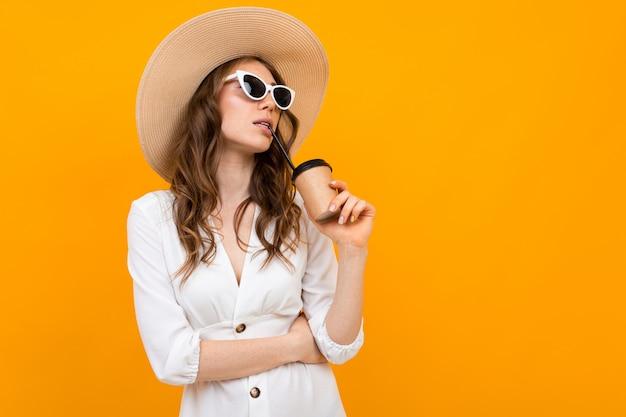 Tajemnicza stylowa dziewczyna w białej sukni na tle żółtej ściany pije kawę