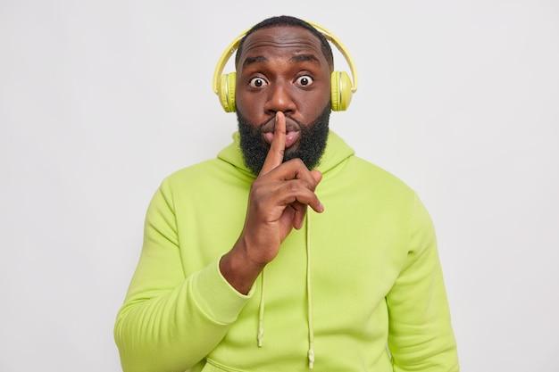 Tajemniczy brodaty mężczyzna robi gest ciszy trzyma palec wskazujący nad ustami, mówi sekretnie słucha muzyki przez słuchawki, ubrany w luźną zieloną bluzę z kapturem na białym tle nad białą ścianą