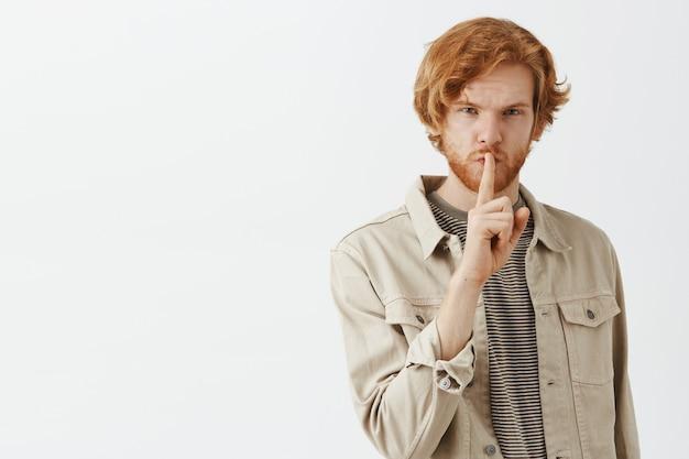 Tajemniczy brodaty rudy facet pozuje przy białej ścianie