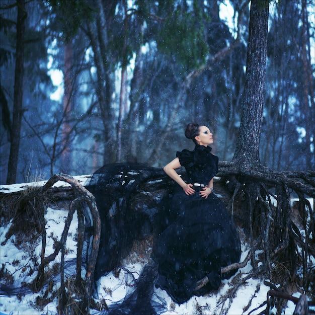 Tajemniczy portret artystyczny pięknej brunetki w długiej czarnej modnej sukni
