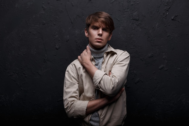 Tajemniczy, poważny młody mężczyzna z modną fryzurą w lekkiej kurtce, w klasycznym swetrze w niebieskich dżinsach stoi i patrzy w kamerę w pobliżu czarnej ściany. europejski przystojny facet