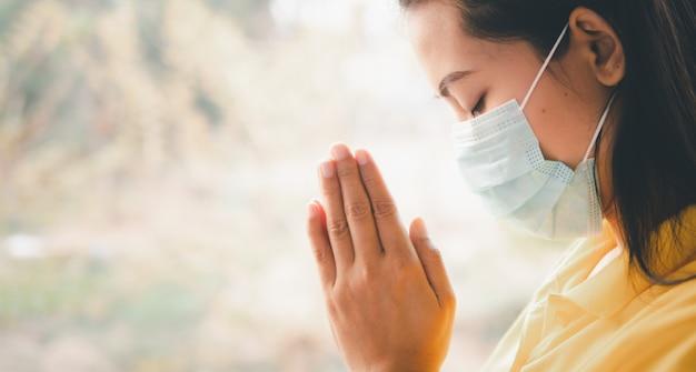 Tajka nosząca maskę w celu ochrony przed wirusem, covid-19 modląca się o błogosławieństwa od boga, aby świat był bezpieczny przed epidemią.