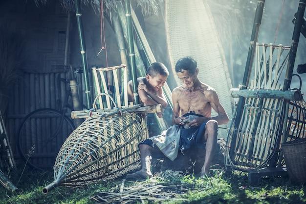 Tajlandia ojciec i syn pracują ręcznie wykonane kosz bambusa lub narzędzi połowowych.