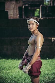 Tajlandzcy bokserzy owijają taśmę w dłonie i stoją na trawniku.