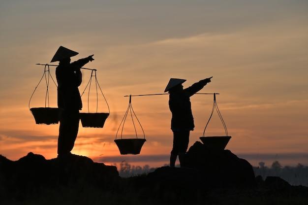 Tajlandzcy rolnicy niosą kosze, aby przygotować się do powrotu do domu przed zachodem słońca. sylwetka rolnika. światło sylwetki.