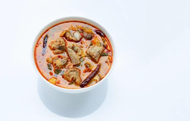 Tajlandzki jedzenie, korzenna polewka z wieprzowina ziobro na białym tle.