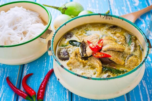 Tajlandzki jedzenie zieleni curry ego kurczak na drewnianym tle.