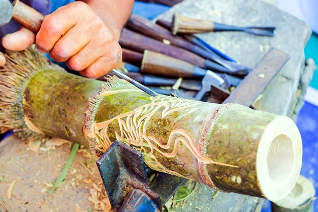 Tajlandzki rzemieślnik używa dłuta wyrzeźbić bambusa