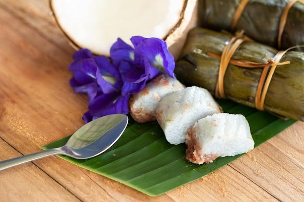 Tajlandzki tradycyjny deserowy kleisty ryż z bananami na drewnianym tle (khao tom mata)