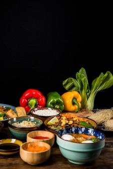 Tajlandzki tradycyjny jedzenie z dzwonkowymi pieprzami i bokchoy nad stołem przeciw czarnemu tłu
